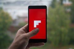 供以人员拿着有Flipboard的智能手机与在屏幕上的手指 库存照片
