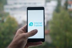 供以人员拿着有Internet Explorer信使商标的智能手机与在屏幕上的手指 免版税库存图片