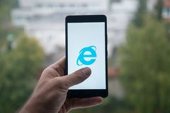供以人员拿着有Internet Explorer的智能手机与在屏幕上的手指 免版税图库摄影