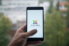 供以人员拿着有Joomla的智能手机与在屏幕上的手指 免版税库存图片