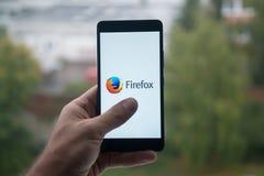 供以人员拿着有Mozilla firefox的智能手机与在屏幕上的手指 免版税库存照片