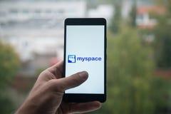 供以人员拿着有Myspace信使商标的智能手机与在屏幕上的手指 免版税图库摄影