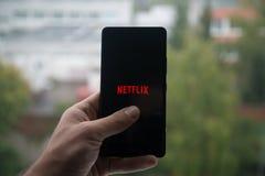 供以人员拿着有Netflix的智能手机与在屏幕上的手指 库存照片