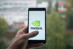 供以人员拿着有Nvidia商标的智能手机与在屏幕上的手指 免版税图库摄影