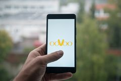 供以人员拿着有Oovoo的智能手机与在屏幕上的手指 库存照片