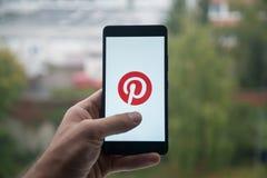 供以人员拿着有Pinterest商标的智能手机与在屏幕上的手指 免版税图库摄影