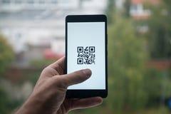 供以人员拿着有QR代码的智能手机与在屏幕上的手指 库存图片