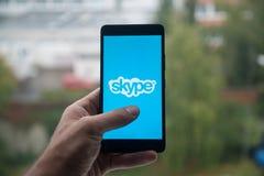 供以人员拿着有Skype的智能手机与在屏幕上的手指 免版税库存图片