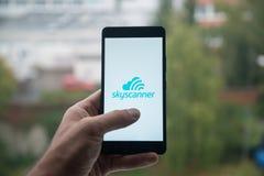 供以人员拿着有Skyscanner的智能手机与在屏幕上的手指 免版税库存图片