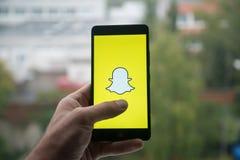 供以人员拿着有Snapchat的智能手机与在屏幕上的手指 库存照片