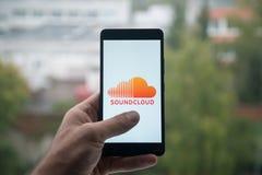 供以人员拿着有Soundcloud信使商标的智能手机与在屏幕上的手指 库存照片