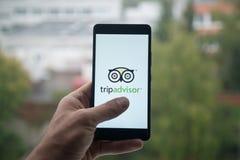 供以人员拿着有Tripadvisor商标的智能手机与在屏幕上的手指 库存图片