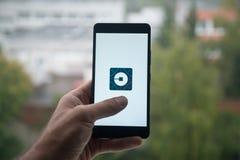 供以人员拿着有Uber信使商标的智能手机与在屏幕上的手指 库存照片