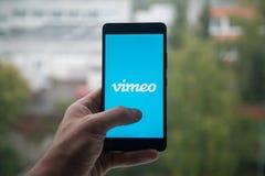 供以人员拿着有Vimeo商标的智能手机与在屏幕上的手指 库存照片