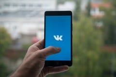 供以人员拿着有Vkontakte商标的智能手机与在屏幕上的手指 免版税库存图片
