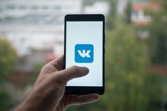 供以人员拿着有Vkontakte商标的智能手机与在屏幕上的手指 图库摄影