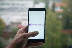 供以人员拿着有Windows电话商标的智能手机与在屏幕上的手指 图库摄影