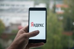 供以人员拿着有Yandex的智能手机与在屏幕上的手指 免版税库存图片
