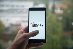 供以人员拿着有Yandex的智能手机与在屏幕上的手指 库存图片