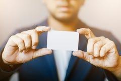 供以人员拿着白色名片,穿蓝色衬衣和显示空白的白色名片的人 被弄脏的背景 水平的mocku 免版税库存照片