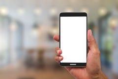 供以人员拿着空白的白色在被弄脏的咖啡馆背景的` s手屏幕手机 免版税库存图片