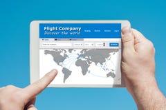 供以人员拿着访问飞行公司网站的片剂设备 免版税库存图片