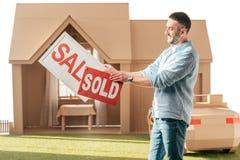 供以人员拿着销售和被卖的牌在纸板房子前面 库存图片
