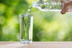 供以人员拿着饮用的瓶装水和倾吐水的` s手入在木桌上的玻璃在与软性的被弄脏的绿色自然背景 免版税图库摄影