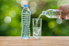 供以人员拿着饮用的瓶装水和倾吐水的` s手入在木桌上的玻璃在被弄脏的绿色自然背景 库存照片