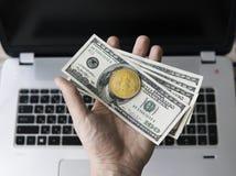 供以人员拿着bitcoin的一枚金黄硬币与的手美元票据反对在背景的一台膝上型计算机 Bitcoin隐藏 库存图片