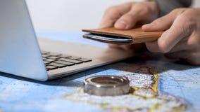 供以人员持护照,预定票在网上在膝上型计算机,计划假期 免版税库存图片