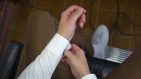 供以人员按钮在袖口袖子豪华白色衬衣的袖扣 关闭人手佩带白色衬衣和链扣 新郎 影视素材