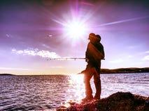 供以人员推挤诱饵和投掷的检查它入海 添加末端象线路标尺的渔夫捕鱼对什么您 库存照片
