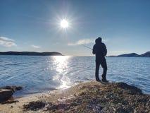 供以人员推挤诱饵和投掷的检查它入海 添加末端象线路标尺的渔夫捕鱼对什么您 图库摄影