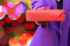 供以人员提供在bokeh形状心脏背景的手一个礼物情人节概念 库存图片