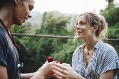 供以人员提议对他愉快的女朋友爱和户外婚姻概念 免版税库存图片