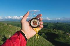 供以人员搜寻与一个指南针的方向在他的在夏天山观点的手上 方向查寻 免版税库存照片