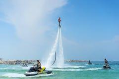 供以人员摆在新的flyboard在加勒比热带海滩 正面人的情感,感觉,喜悦 做假期的滑稽的逗人喜爱的人  免版税图库摄影