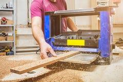 供以人员擦试在一个thicknessing的机器的一个木板 免版税库存图片