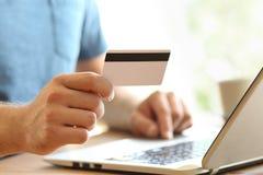 供以人员支付在与信用卡的线的手 库存图片