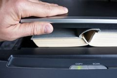 供以人员放书的手入一个复制的设备 免版税库存图片