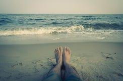供以人员放松在与海的一个海滩和在背景减速火箭的作用的沙滩的脚 库存图片