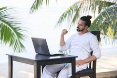 供以人员放松在与膝上型计算机的海滩,自由职业者展示胜利 免版税库存图片