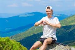供以人员放松在小山和赞赏的美好的山谷视图顶部的远足者 免版税库存图片
