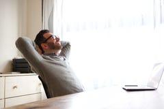供以人员放松用在头后的手在膝上型计算机前面 免版税库存照片
