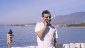 供以人员旅客谈话在电话,微笑,在海/海洋的背景 连接和通信的概念 股票录像