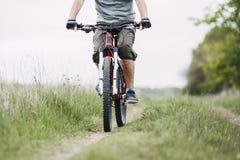 供以人员旅行骑沿乡下公路的一辆自行车 免版税库存照片