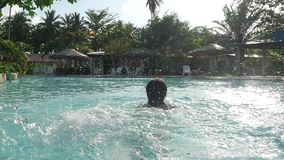 供以人员晒日光浴,放松和游泳在水池在慢动作的晴天 水在一美好的晴朗的bokeh飞溅 影视素材