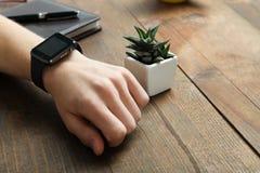 供以人员有一块巧妙的手表的` s手 库存图片