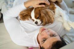 供以人员有与狗的好时光在沙发早晨 在家使用骑士的国王查尔斯狗 免版税库存图片
